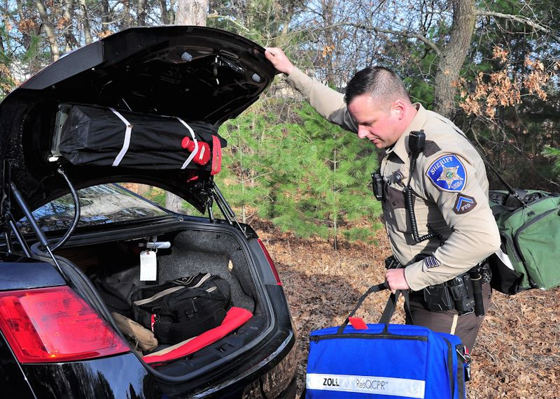 Image of deputy getting gear out of squad trunk
